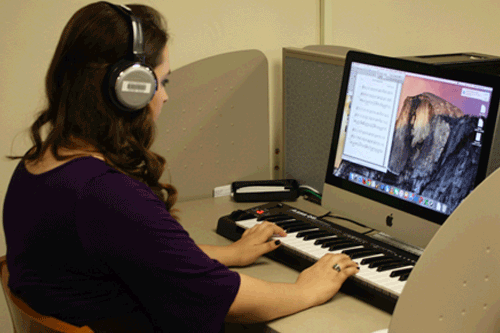 Photo of student writing music at the computer.